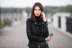 Close up emotional portrait of a young pretty brunette woman posing full length outdoors city park wearing black leather coat hold Royalty Free Stock Photography