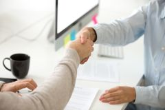 Close up of employer shaking hand of male job applicant royalty free stock photography