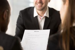 Close up of employers or recruiters holding reviewing cv resume. Close up of employers or recruiters holding reviewing cv of happy applicant smiling at royalty free stock photography