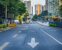 Close up empty asphalt road on city street with road markings in the form of arrow. China, Shenzhen, 2018-03-09:  Close up empty asphalt road on city street Royalty Free Stock Images