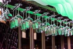 Empty glasses hang over bar rack stock photography