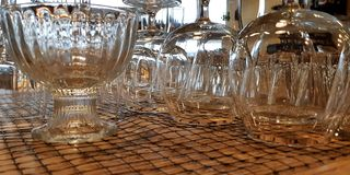 Pile of empty transparent glasses on shelf. Close up of transparent clean glasses on a shelf, nested upside down stacked stock images