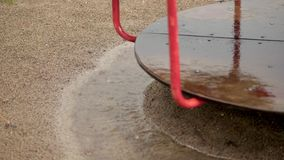 Close-up, Empty merry go round carousel is wet in the rain, turns lonely in wind. a heavy rain, downpour with a strong. Wind. large puddles on the playground stock footage