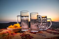 Close up empty mugs of beer on a sunrise background with mountains. Beer party is over concept. stock image