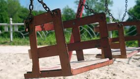 Close-up of empty old rusty swing swinging in summer park. Slow motion.