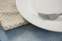 Close up of empty plate with fork and napkin Royalty Free Stock Photography