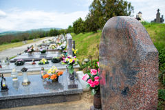 Close up of empty tombstone. Graves, tomb stones and crucifixes on traditional public cemetery. Votive candles lantern and flowers on tomb stones on graveyard royalty free stock photo