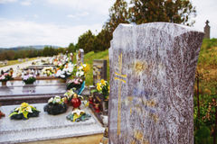 Close up of empty tombstone. Graves, tomb stones and crucifixes on traditional public cemetery. Votive candles lantern and flowers on tomb stones on graveyard royalty free stock photos