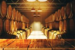 Winery and alcohol concept. Close up of empty wooden table with blurry wine barrels in the background. Winery and alcohol concept. 3D Rendering Stock Images