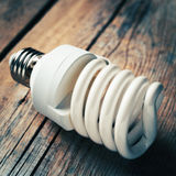 Close up of energy saving light bulb on wooden desk. Vintage sty Stock Photos