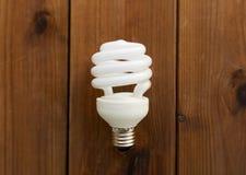 Close up of energy saving lighting bulb on wood Stock Photo
