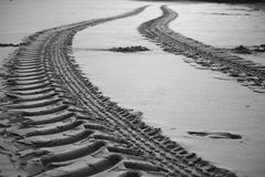 Close-up of engine tyre trace on a sandy beach in early morning Stock Photo