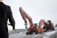 Close up of engineer hand holding white safety helmet for workers security standing in front of blurred construction site with cra Stock Photos