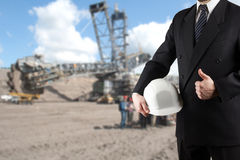 Close up of engineer hand holding white safety helmet for workers security standing in front of blurred construction site with cra Stock Images