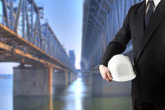 Close up of engineer hand holding white safety helmet for workers security standing in front of blurred construction site with cra Stock Photography