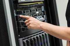 Close-up of IT Engineer Switching On Server At Datacenter. Close-up of adult male IT engineer switching on server at datacenter Stock Photos