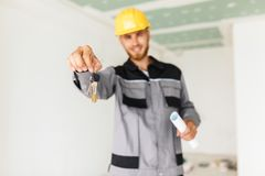 Close up engineer in work clothes and yellow hardhat happily hol. Ding keys of new apartment in hand Stock Images