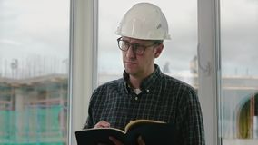 Engineer writing in a notebook. Close up.Engineer writing in a notebook. Professional shot in 4K resolution. 025. You can use it e.g. in your commercial video stock footage