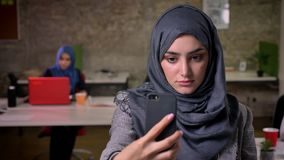 Close-up enjoyable arabian female in beautiful hijab is taking selfie on her phone while standing on brick background. Working modern mood stock footage
