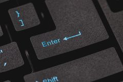 Enter Key on a Computer Keyboard. Close up of an Enter key in blue on a black key on a new computer keyboard Stock Photography