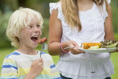 Close up of enthusiastic boy taking a bite of barbecued sausage Stock Photos