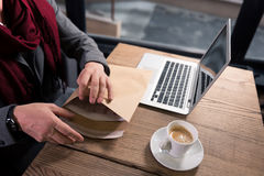 Close up of an envelope with documents. Sending the letter. Close up of a big paper envelope being filled with documents while being in hands of a handsome stock photography
