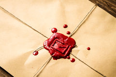 Close-up on an envelope with red sealing wax and old thin rope. On old wooden table Royalty Free Stock Photos