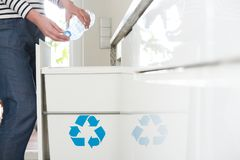 Aware housewife recycling plastic bottles. Close-up of environmentally aware housewife segregating plastic bottles in the kitchen royalty free stock image