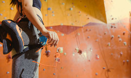 Close up of equipped woman standing behind the climbing wall. Royalty Free Stock Photo