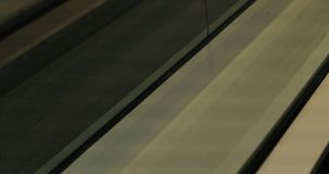 Close-up of an escalator. A woman with a suitcase on wheels riding an escalator stock footage