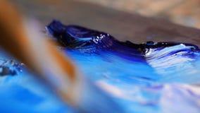 Close-up A escova toma a pintura azul na paleta, dilui a cor 4K mo lento filme