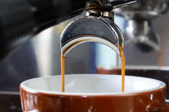 Close-up of espresso pouring from coffee machine. Royalty Free Stock Photo