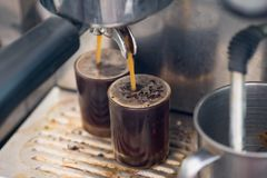 Close up of espresso pouring from coffee machine to shot glass. Professional coffee brewing stock photography