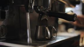 A close-up of espresso pouring from a professional coffee machine into two steel pitches stock footage