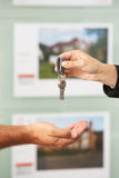 Close Up Of Estate Handing Over Keys Of New Home. To Client Stock Photo