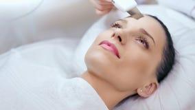 Close-up etalon vrouwelijk jong gezicht met perfecte huid tijdens ultrasone schil bij schoonheidssalon stock videobeelden