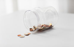 Close up of euro coins in big glass jar on table Stock Image
