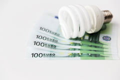 Close up of euro money and light bulb on table Stock Photos