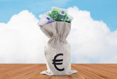 Close up of euro paper money in bag on table. Business, finance, investment, saving and cash concept - close up of euro paper money in bank bag over blue sky and stock photography