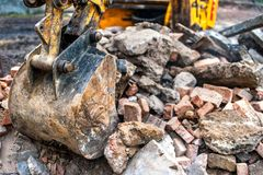 Close-up of excavator bucket loading rocks, stones, earth. And concrete bricks from demolition site Stock Photography