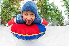 Close-up of excited boy on snow tube in winter. Close-up view of excited boy on snow tube in winter during day in the fir tree forest Royalty Free Stock Photography