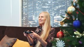 Close up of excited woman loses game on playstation near the Christmas tree. There are skyscrapers in the background stock footage