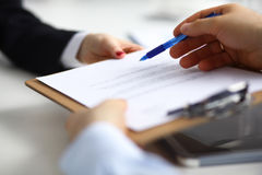 Close up of an executive hands holding a pen and indicating where to sign a contract at office stock photo