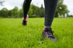 Close up of exercising woman legs on grass in park Royalty Free Stock Photography