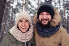 Close-up of exhilarated family during the winter walk. Low angle of happy couple standing in the wintry forest. Couple posing at the camera. Beautiful landscape Royalty Free Stock Images