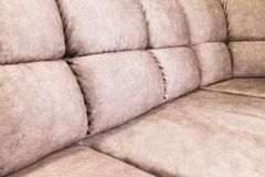 Close-up of an expensive soft textile sofa of beige color with brown shades. Interior Background stock photography