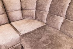 Close-up of an expensive soft textile sofa of beige color with brown shades. Interior Background royalty free stock images