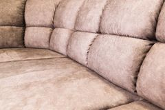 Close-up of an expensive soft textile sofa of beige color with brown shades. Interior Background stock image