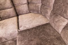 Close-up of an expensive soft textile sofa of beige color with brown shades. Interior Background stock photos