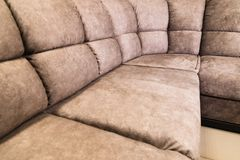 Close-up of an expensive soft textile sofa of beige color with brown shades. Interior Background royalty free stock image